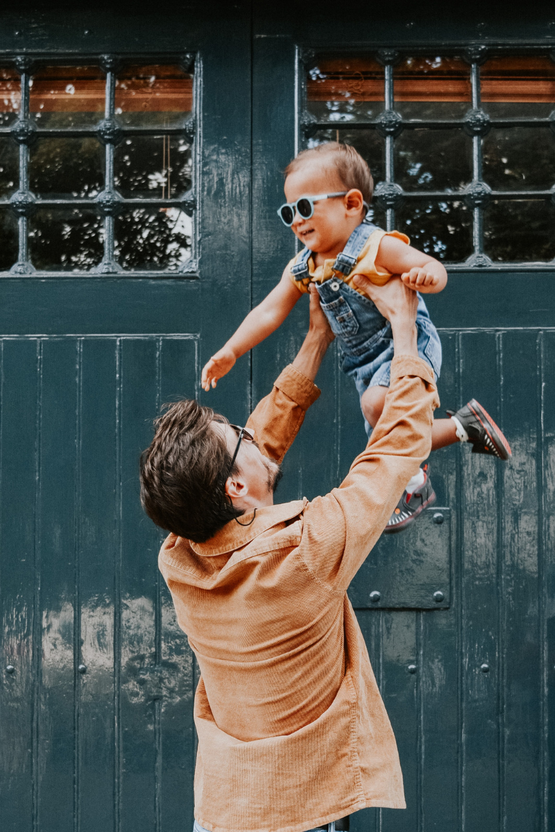 Father in orange shirt lifts child in dungarees and sunglasses into the air in front of green wooden door